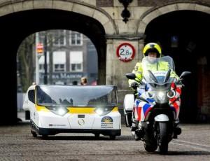© ANP. De Stella-zonneauto rijdt richting het Binnenhof in Den Haag, maart 2014.